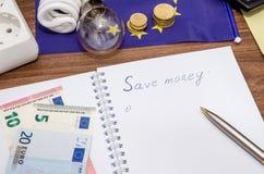 Gloeilampen op Europese bankbiljetten met lege blocnote en pen Stock Foto
