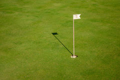 Glof flag mark in hole throwing shadow on the green course grass Royalty Free Stock Image