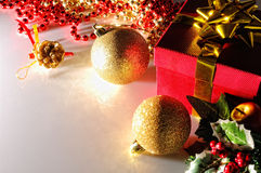 Gloom Christmas decoration with two balls and gift top view. Gloom Christmas decoration on a white methacrylate table. Red gift box with gold ribbon, two golden royalty free stock image
