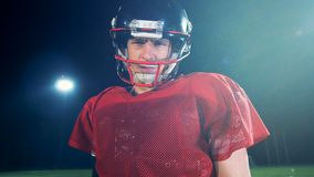 Gloomy american football player is looking straight into the camera