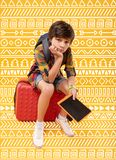 Gloomy child feeling tired while sitting on the luggage. Tired boy. Tired teenage boy holding a modern tablet and sitting with his head resting on his hand while Stock Photography