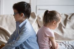 Gloomy children sitting on couch at home royalty free stock photography