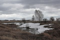 Gloomy cold spring in Siberia cloudy landscape melts snow in the fields. Gloomy cold spring in Siberia cloudy landscape snow melts in the fields dry grass stock photography