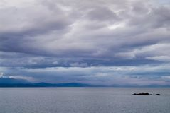 Gloomy day sea landscape with a rainy cloudy sky. Bay and rocks. At background Stock Image