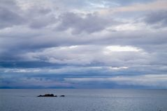 Gloomy day sea landscape with a rainy cloudy sky. Bay and rocks. At background Royalty Free Stock Image