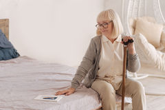 Gloomy depressed woman sitting on the bed. Feeling of loneliness. Gloomy depressed aged woman holding a walking stick and looking at the photograph of her Stock Images