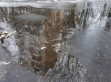 Gloomy diagonal reflection of a large house in brown puddle on wet asphalt, bare branches of a tree, the snow melts. Royalty Free Stock Photo