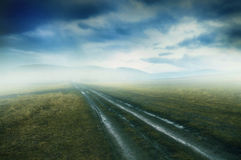 Gloomy dirty country road with meadow mist and dramatic cloudsca Stock Photo