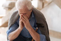 Gloomy elderly man crying. So many emotions. Gloomy cheerless elderly man sitting with a walking stick and crying while not being able to hold his emotions royalty free stock photography