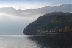 Gloomy fall day on lake Como, Italy. Beautiful view of lake Como (Italy) in autumn with canoes Stock Images