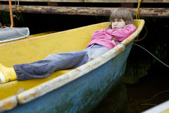 Gloomy girl lying on yellow boat Stock Photo