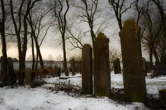 Gloomy Grave Yard. Three grave stones on a winter cemetery, covered with snow and surrounded with trees. The picture has a gloomy atmosphere stock image