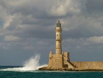 Gloomy gray clouds hang over the lighthouse of yellow and white bricks in Chania, about which waves crash stock photo
