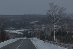 Gloomy grey empty winter road in the hills. Royalty Free Stock Photo