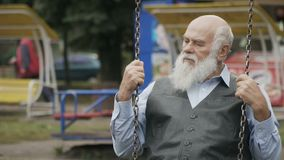 Gloomy grey-haired old man swings in slowmotion stock video footage