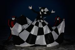 Gloomy haleyquins and chess queen at night Royalty Free Stock Photos
