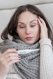 Gloomy ill woman having a high fever. Being sick. Cheerless gloomy ill woman holding a body thermometer and looking at it while suffering from a high fever Stock Photo