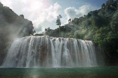 Gloomy jungle waterfall. Panoramic view on a back lit spooky and gloomy wide majestic waterfall and surrounding tropical jungle, with sun, sun rays and hazy Royalty Free Stock Photos