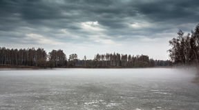 Gloomy landscape on frozen misty lake in season between winter and spring Royalty Free Stock Photography