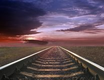 Gloomy landscape with rails going away into the far sunset. Evening landscape with rails Stock Images