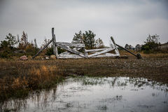 Gloomy landscape with old broken wood fence and marsh Royalty Free Stock Photos