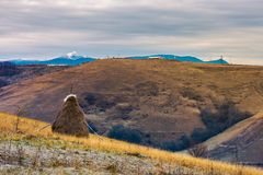 Gloomy late autumn in mountainous rural area. Haystack on a step slope. mountain with snowy peak in the distance. gloomy late autumn in mountainous rural area royalty free stock photos
