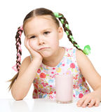Gloomy little girl doesn't want to drink milk Stock Image