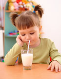 Gloomy little girl drinks milk. In preschool Stock Image