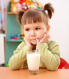 Gloomy little girl drinks milk Royalty Free Stock Photos