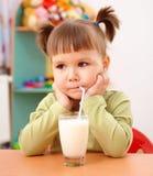 Gloomy little girl drinks milk. In preschool Royalty Free Stock Photos