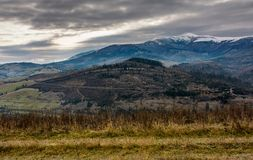 Gloomy morning in mountains. Autumnal scenery with snowy mountain tops Royalty Free Stock Photo