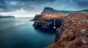 Gloomy morning scene of Mulafossur Waterfall. Dramatic autumn view of Gasadalur village, Vagar, Faroe Islands, Kingdom of Denmark,