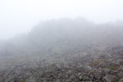 Gloomy mountain landscape. Fog in the mountains, the gloom comes down from the mountains. Mountain placer in the fog. Stones in the fog Stock Photo