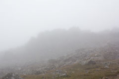 Gloomy mountain landscape. Fog in the mountains, the gloom comes down from the mountains. Mountain placer in the fog. Stones in the fog Royalty Free Stock Photography