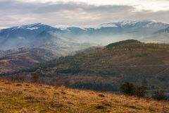 Gloomy november scenery in mountains. Foggy and hazy forenoon on an overcast day. distant mountain tops in snow royalty free stock images