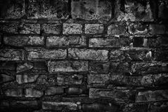 Gloomy old black brick wall - sinister dark background stock photo