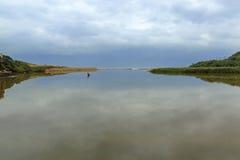 Gloomy Overcast Sky and Coastal Vegetation Reflections on Water Stock Photos