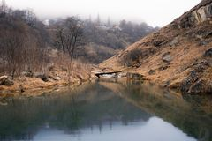 Gloomy quiet pond in a mountainous area with fog. Photo royalty free stock image