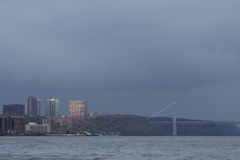 Gloomy rain clouds after Hurricane Sandy. Sunlight and dark rain clouds along Hudson River the day after Hurricane Sandy hit Manhattan Royalty Free Stock Photos