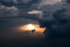 Gloomy sunset. Sunset with dark dark clouds and the sun, which makes its way through them Royalty Free Stock Photography