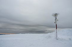 Gloomy winter landscape with frozen sign showing directions Royalty Free Stock Images