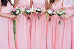 Glorierijke bruidsmeisjes die in roze kleding mooie bloemen houden Stock Fotografie