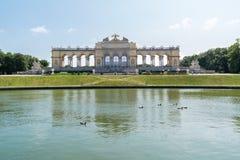 Gloriette in Schonbrunn Palace Gardens, Vienna. Gloriette belvedere and cafe with people, tourist train and pool in Schonbrunn Palace Gardens, Vienna, Austria Stock Photo