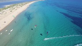 Stunning 4k drone aerial panorama seascape of people kitesurfing in clear blue turquoise ocean water on windy summer day. Glorious aerial drone seascape panorama stock video footage