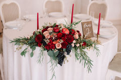 Glorious autumn bouquet on guest wedding table. Glorious autumn bouquet with roses, apples and grapes on decorated with candlesticks, numbered guest wedding royalty free stock images