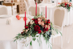 Glorious autumn bouquet on guest wedding table. Glorious autumn bouquet with roses, apples and grapes on decorated with candlesticks, numbered guest wedding Royalty Free Stock Image