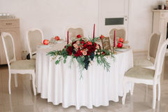 Glorious autumn bouquet on guest wedding table. Glorious autumn bouquet with roses, apples and grapes on decorated with candlesticks, numbered guest wedding Royalty Free Stock Photos