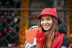 Glorious blonde girl wearing red hat and knitted scarf holding g. Glorious blonde woman wearing red hat and knitted scarf holding gift box. Empty space stock photo