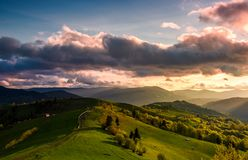 Glorious cloudy sunset over rural area. Beautiful springtime landscape with mountain ridge in the distance. country road winds through grassy slopes on rolling Royalty Free Stock Photo