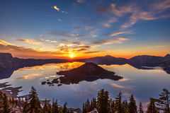 Glorious Crater Lake Sunrise. Glorious light as the sun is rising at Crater Lake National Park, Oregon. Perfect reflection and silhouette of wizard island stock photo